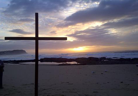 Easter at dawn. Cross on the beach with sunrise behind.